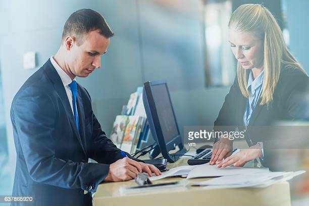 Businessman signing an insurance contract at a counter