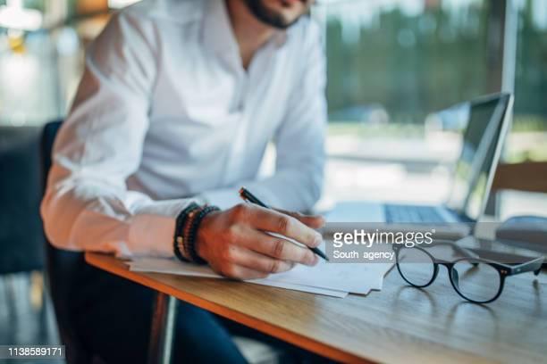 contrat de signature d'homme d'affaires dans le café - engagement photos et images de collection