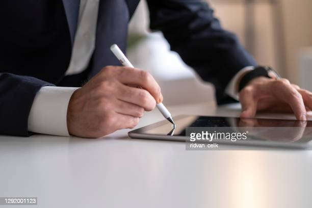 businessman signing digital contract on tablet using stylus pen - contract stock pictures, royalty-free photos & images