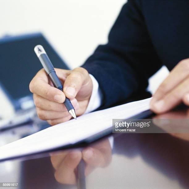 Businessman signing document at desk, close-up of hands