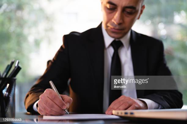 businessman signing legal paper in office - article stock pictures, royalty-free photos & images