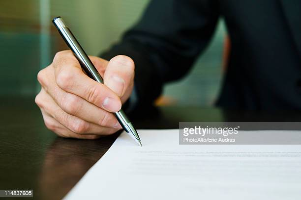 Businessman signing paperwork, cropped