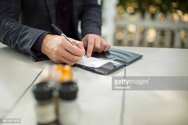 Businessman signing the bill at restaurant