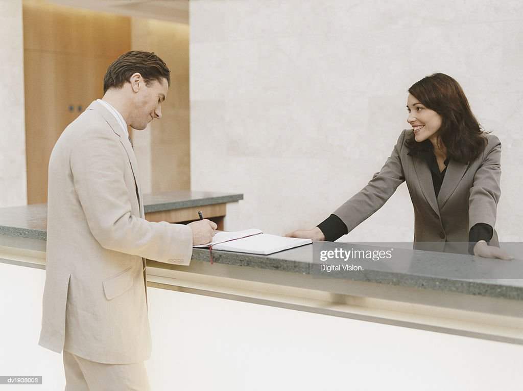 Businessman Signing the Guestbook at a Reception Desk : Stock Photo