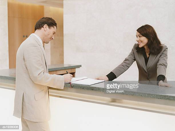 Businessman Signing the Guestbook at a Reception Desk
