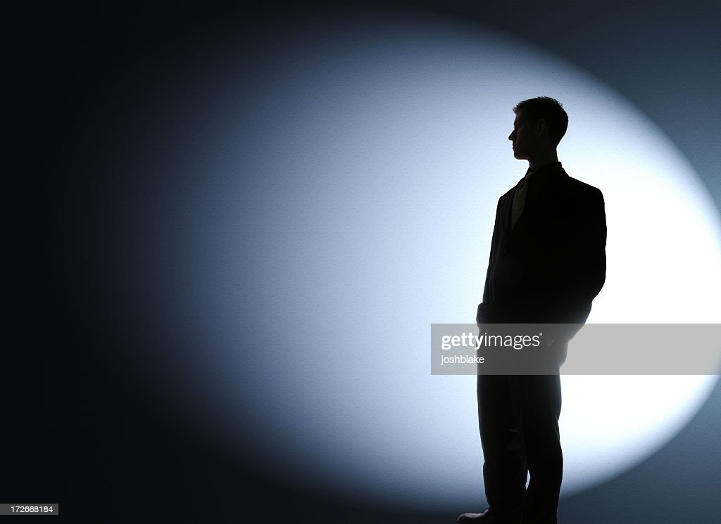Businessman silhouetted in a spotlight : Stock Photo
