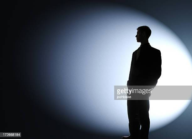 businessman silhouetted in a spotlight - spotlit stock pictures, royalty-free photos & images