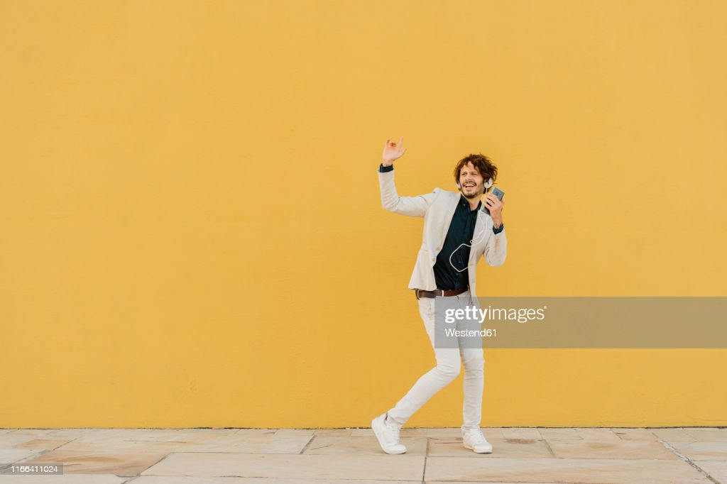 Businessman singing and dancing in front of yellow wall listening music with headphones and smartphone : Stock Photo