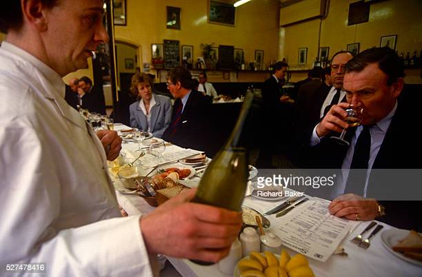 Businessman sips a chilled glass of white wine to accompany a dish of seafood in Sweetings in the City of London. A waiter waits for the man's...