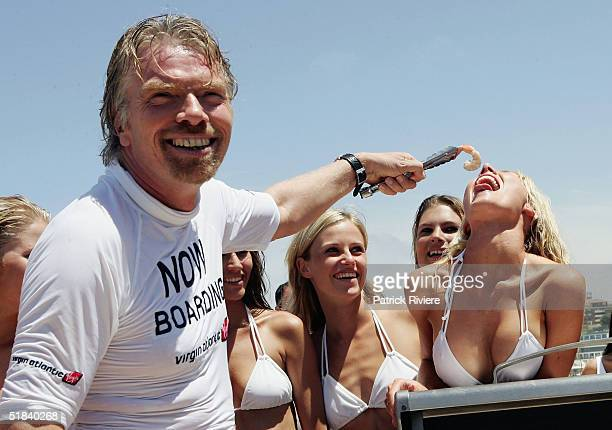 Businessman Sir Richard Branson helps a model to eat a prawn on Bondi Beach during his visit to launch his new Virgin Atlantic airline venture...