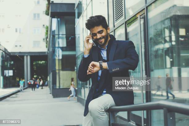 Businessman sit in front of the building talking on mobile and checking time on watch.