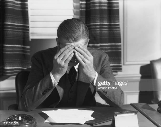 Businessman sits at his office desk, his forehead held in his hands, his elbows propped up on the desk before him, circa 1945. An ashtray and...