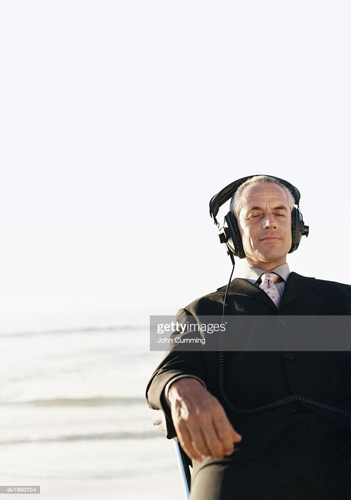 Businessman Sits at the Water's Edge in a Chair, Listening to Music on Headphones : Stock Photo