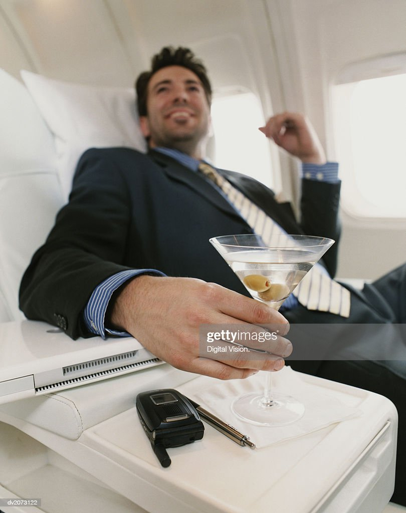 Businessman Sits in a Plane Holding a Martini, Focus on the Foreground : Stock Photo