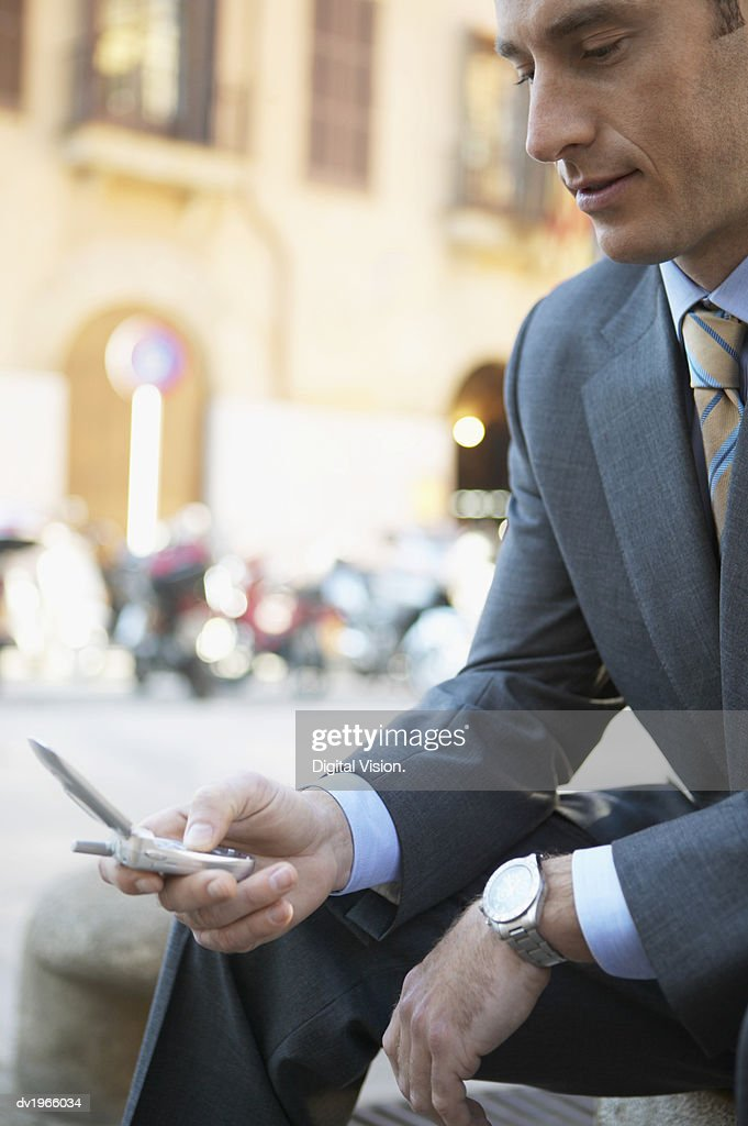 Businessman Sits in an Urban Setting Texting on His Mobile Phone : Stock Photo