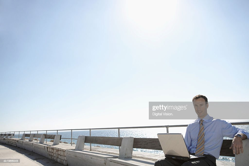 Businessman Sits on a Bench by the Sea, Using a Laptop : Stock Photo