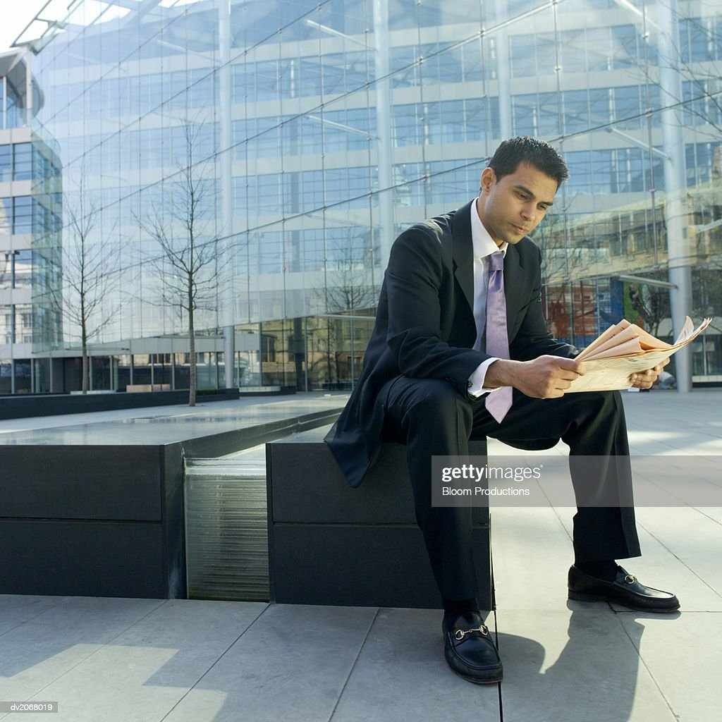 Businessman Sits on a Bench Reading a Newspaper : Stock Photo