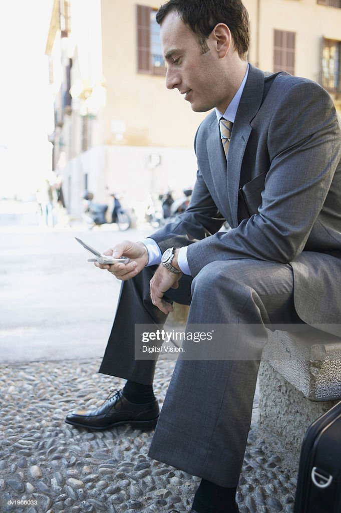 Businessman Sits on a Stone Bench, Texting on His Mobile Phone : Stock Photo