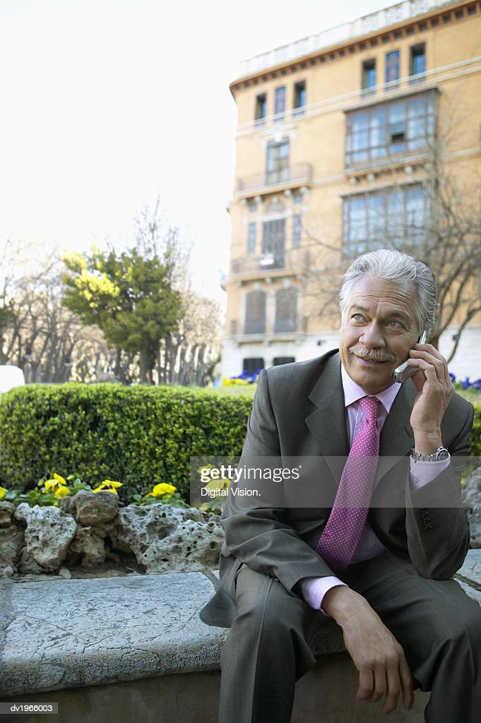 Businessman Sits Outside Using His Mobile Phone : Stock Photo