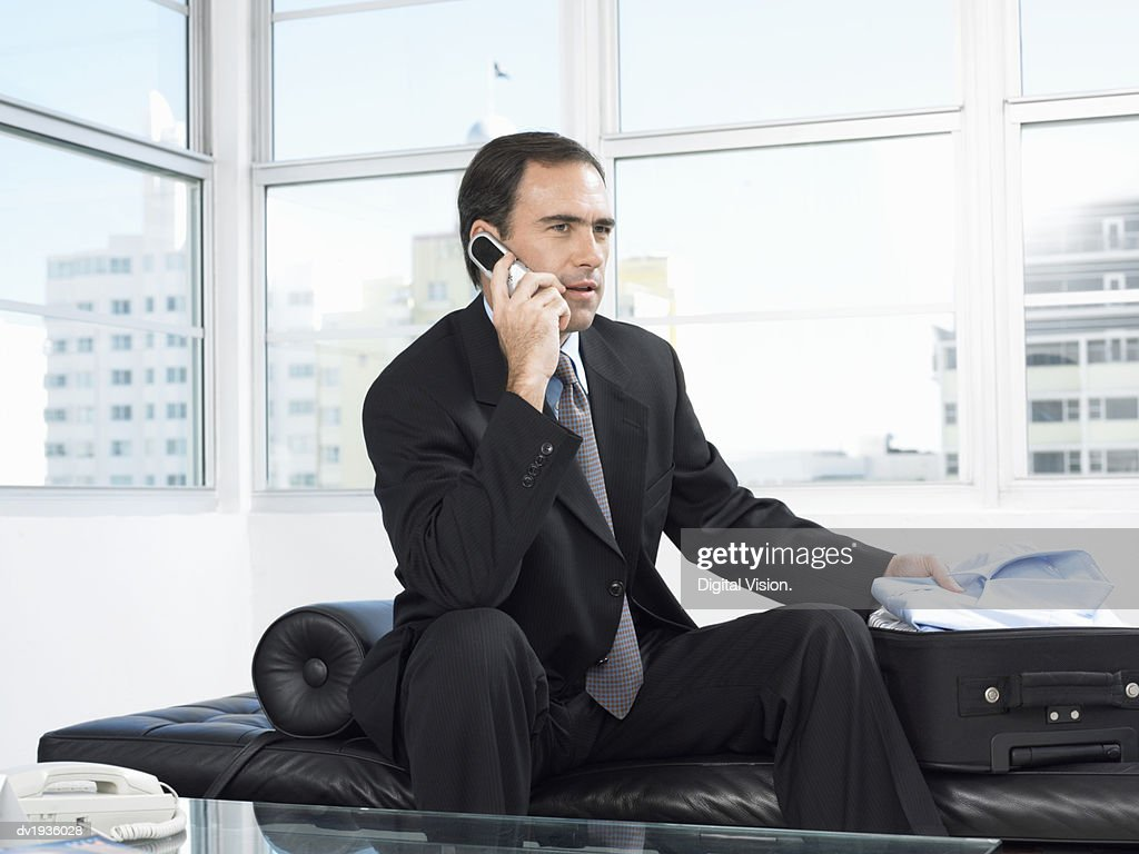 Businessman Sits Talking on a Mobile Phone While Unpacking a Suitcase : Stock Photo