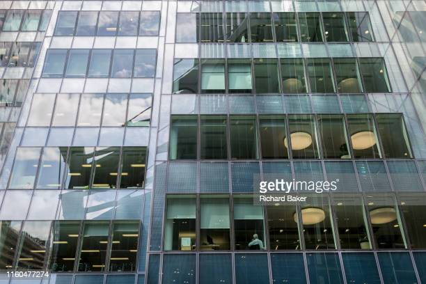 A businessman sits with his back to the window on a lower floor of his corporate office building in the City of London the capital's financial...