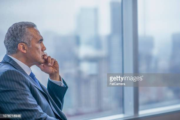 businessman sitting alone in a boardroom - chairperson stock pictures, royalty-free photos & images