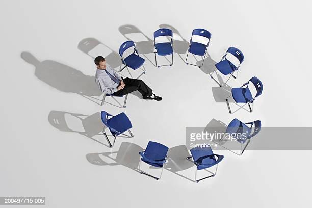 businessman sitting alone in circle of chairs, elevated view - cadeira dobrável - fotografias e filmes do acervo