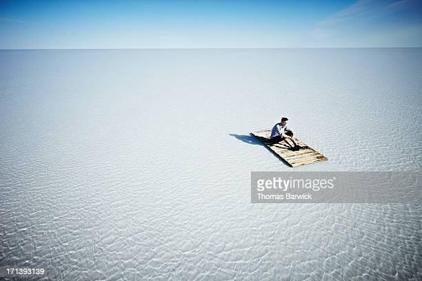 Businessman sitting alone on life raft