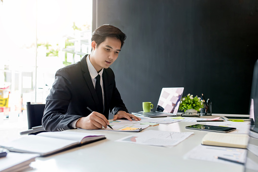 Businessman sitting analyze document information in the workplace. 1095884900