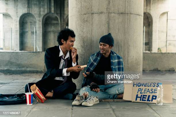 a businessman sitting and eating a meal with the homeless - homelessness stock pictures, royalty-free photos & images