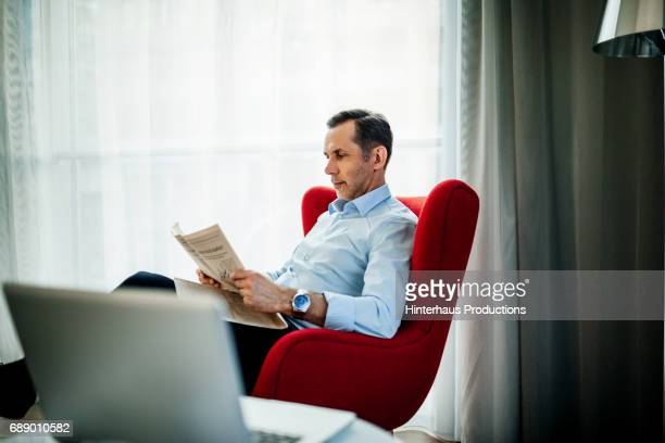 Businessman Sitting And Reading In Hotel Room