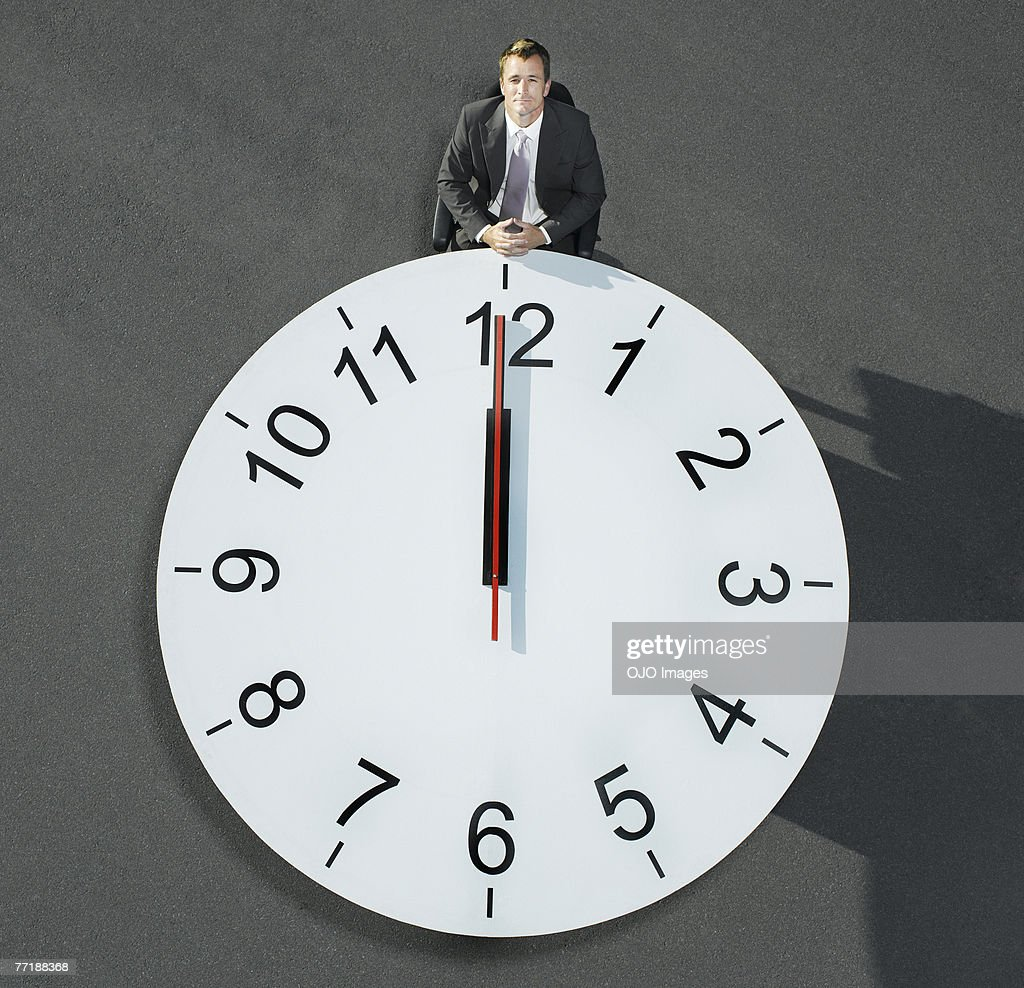 A businessman sitting at a clock table : Stock Photo