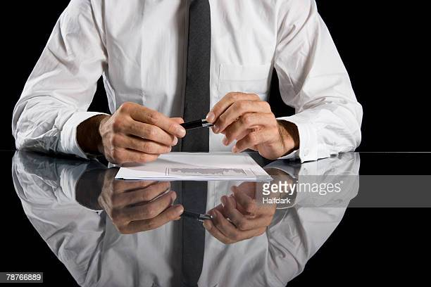 A businessman sitting at a desk and holding a pen