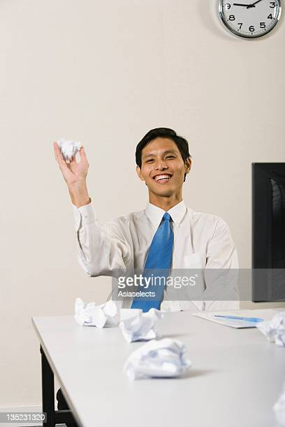 Businessman sitting at a desk and throwing crumpled papers in an office