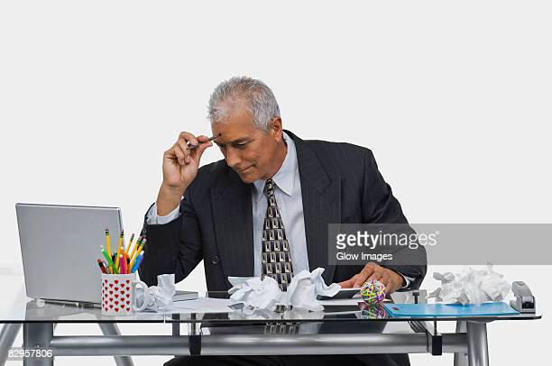 Businessman sitting at a desk with crumpled papers on the desk