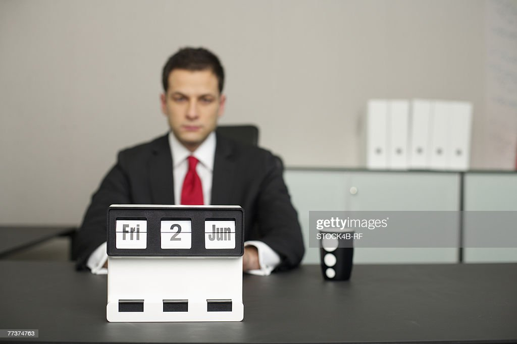 Businessman sitting at a table, calendar in foreground : Photo