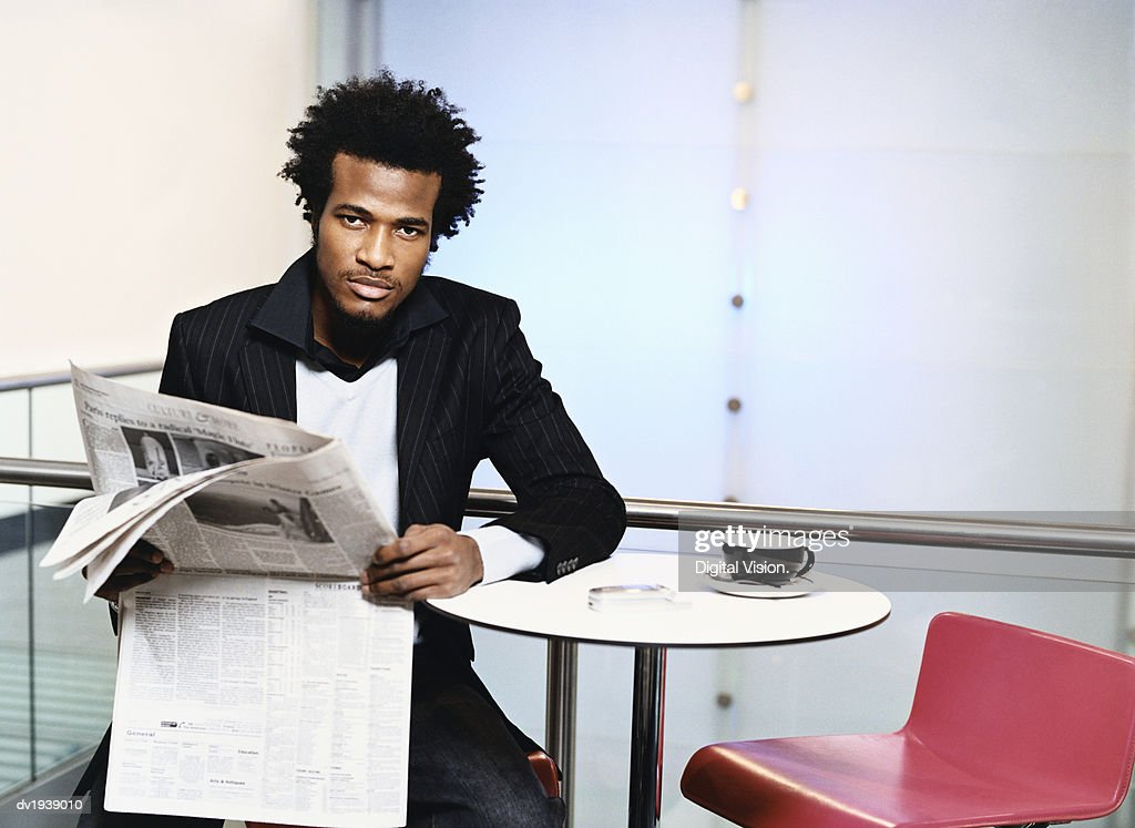 Businessman Sitting at a Table Holding a Newspaper : Stock Photo