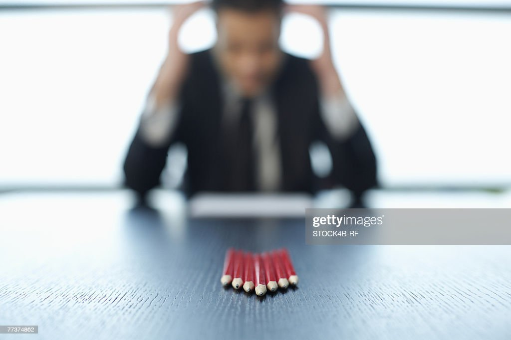 Businessman sitting at a table, pencils in foreground : Stockfoto