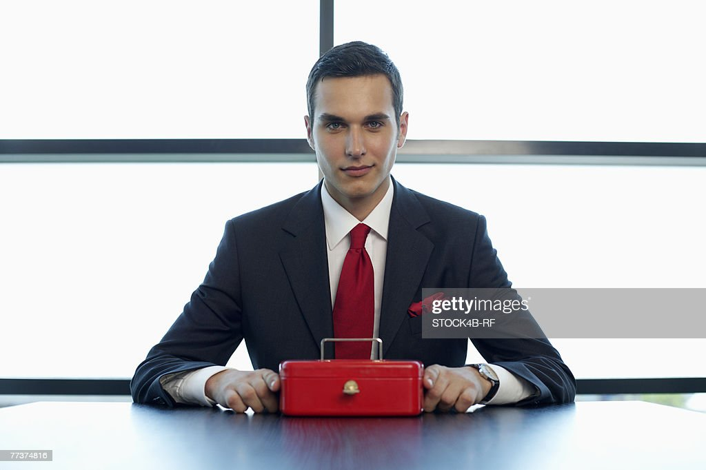 Businessman sitting at a table with a cash box : Photo