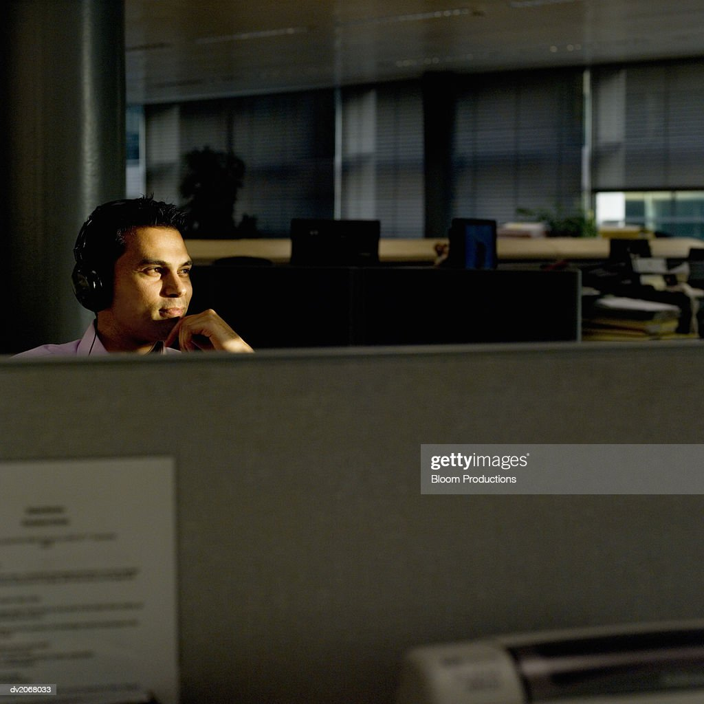 Businessman Sitting at an Office Desk at Night, Wearing Headphones : Stock Photo
