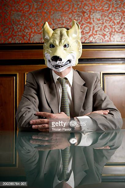 Businessman sitting at boardroom table wearing mask of wolf's face