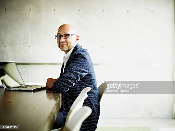 businessman sitting at conference room table - differential focus stock pictures, royalty-free photos & images