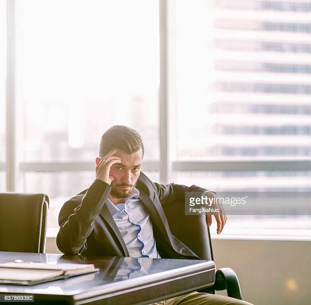 Businessman sitting at conference table in office