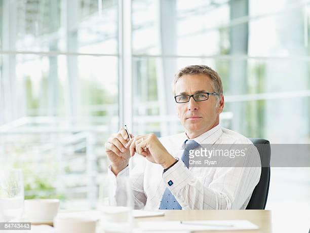 businessman sitting at conference table - one man only stock pictures, royalty-free photos & images