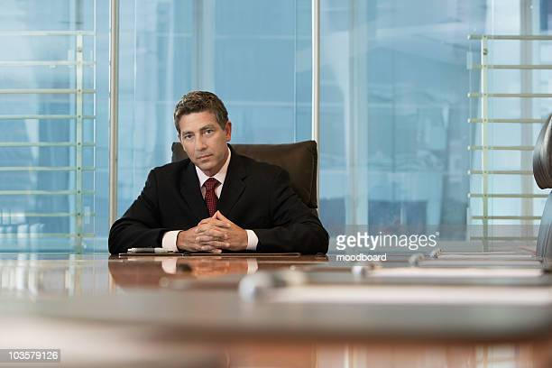 Businessman sitting at conference table, portrait