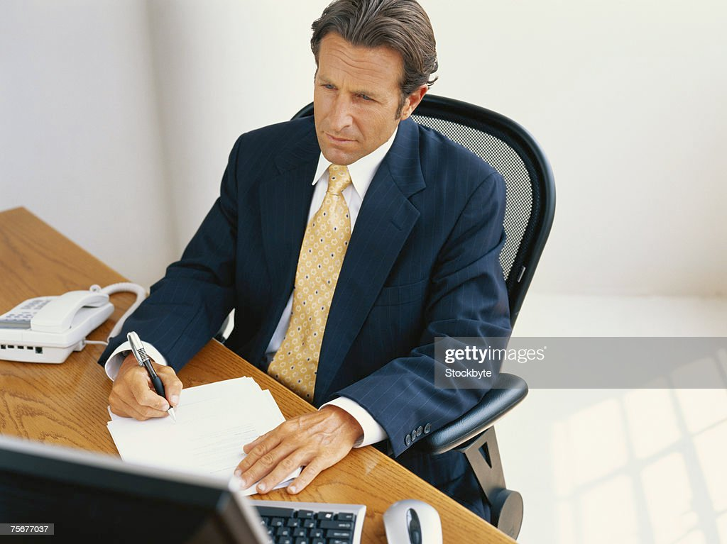 Businessman sitting at desk and writing, elevated view : Stock-Foto