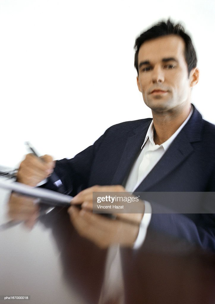 Businessman sitting at desk, blurred, portrait : Bildbanksbilder