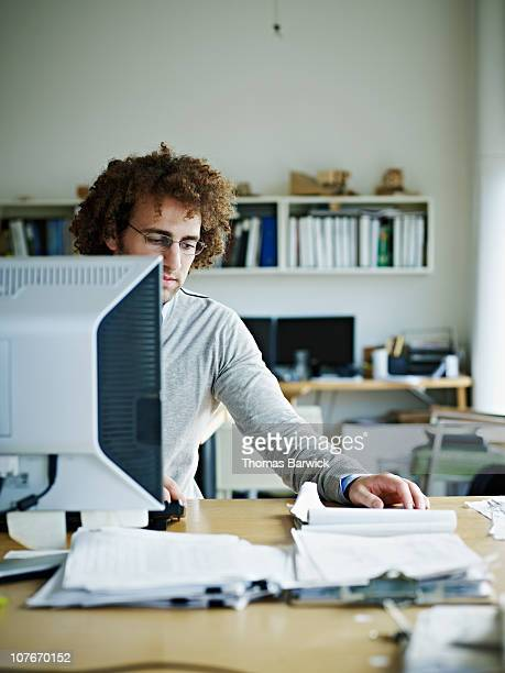 Businessman sitting at desk examining documents