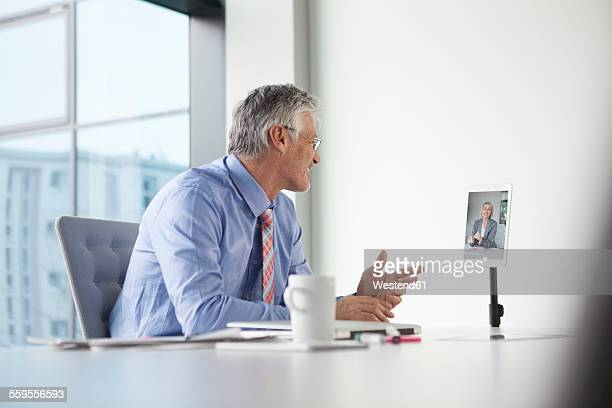 Businessman sitting at desk having video conference