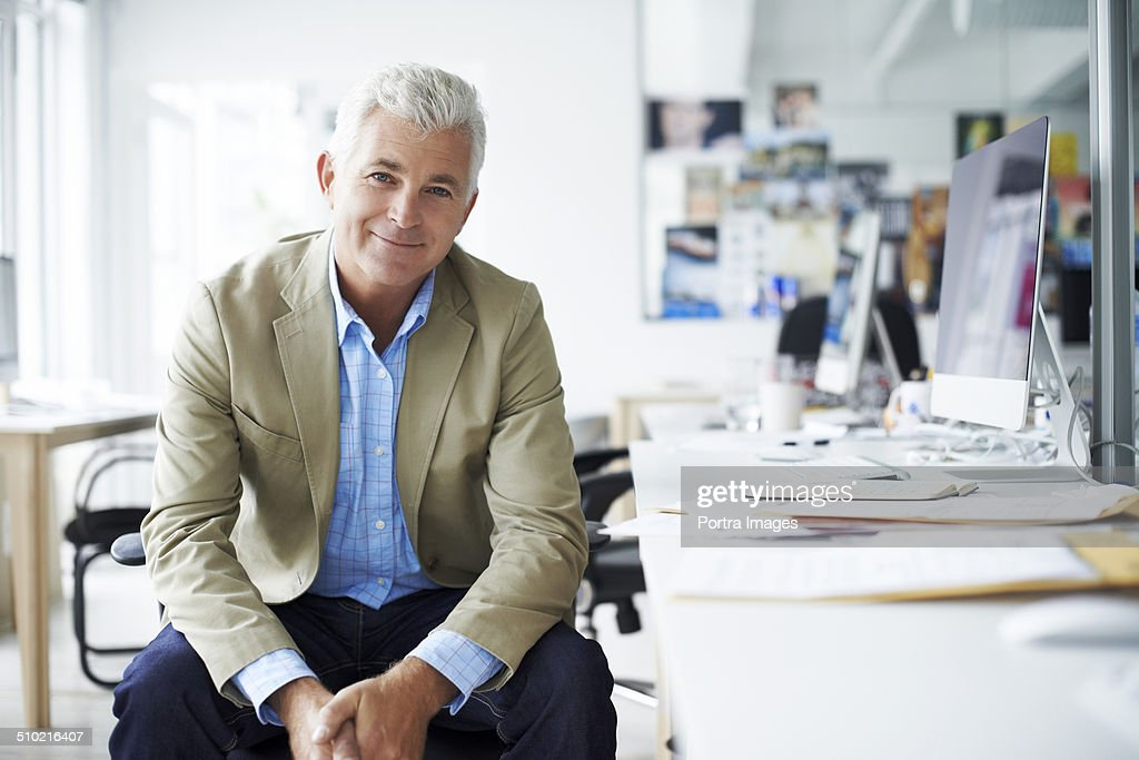 Businessman Sitting At Desk In Creative Office Stock Photo